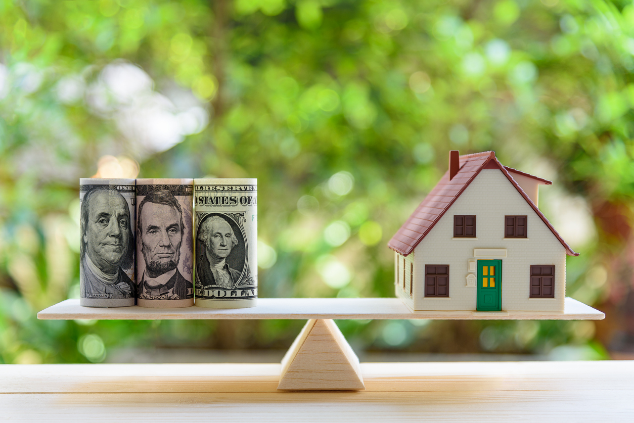 Home loan / reverse mortgage or transforming assets into cash concept : House model, US dollar notes on a simple balance scale, depicts a homeowner or a borrower turns properties / residence into cash
